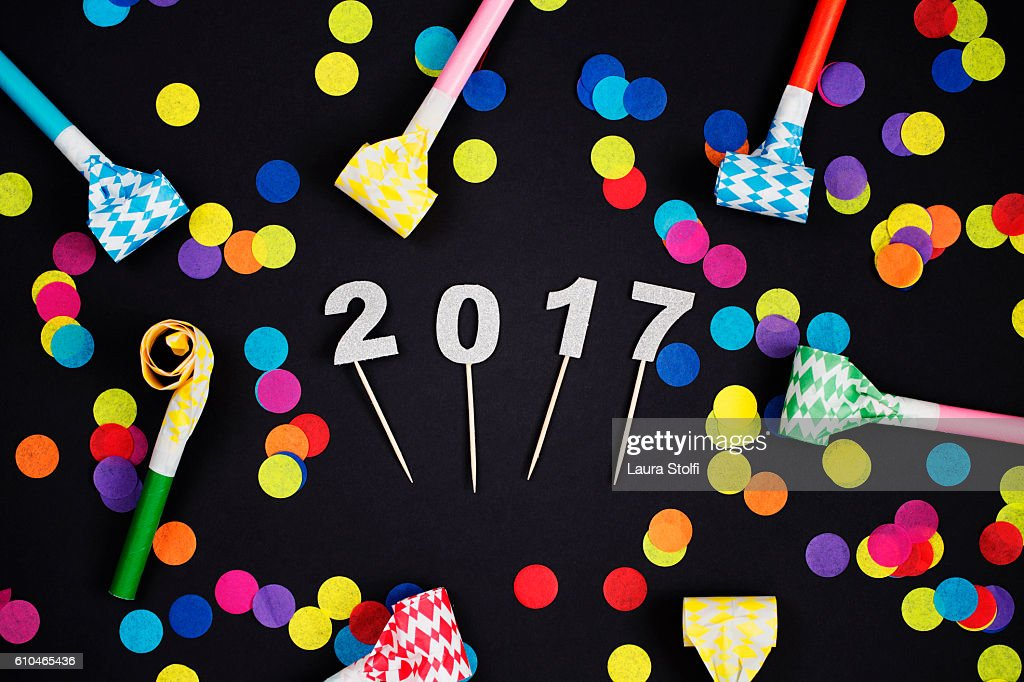 Glittery 2017 numbers amongst colorful confetti and party horns : Stock Photo