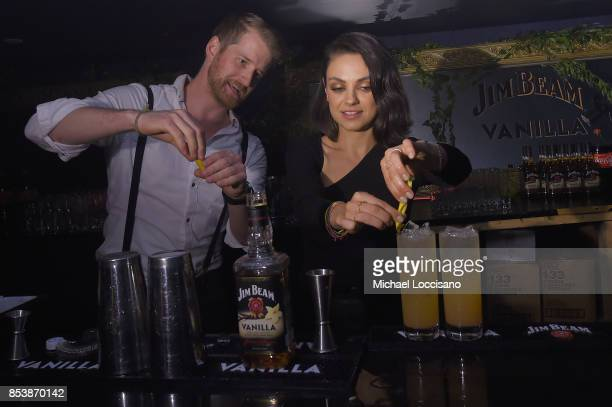Global brand partner Mila Kunis assists a bartender showing guests how to achieve the perfect balance of bourbon and cola at the exclusive Jim Beam®...