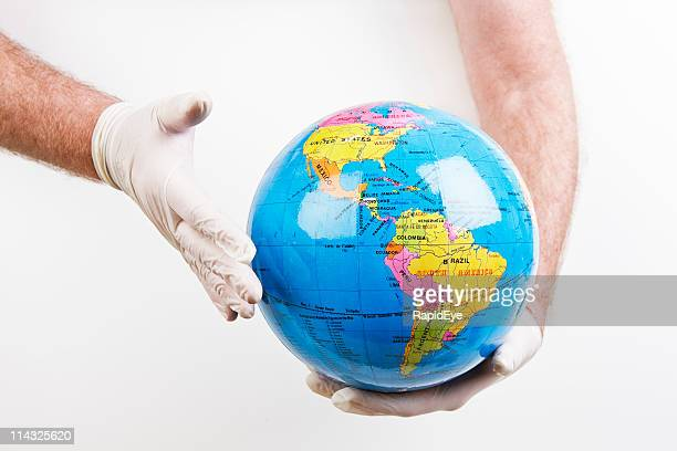 global health | doctor wearing gloves holds globe - world health organization stock pictures, royalty-free photos & images
