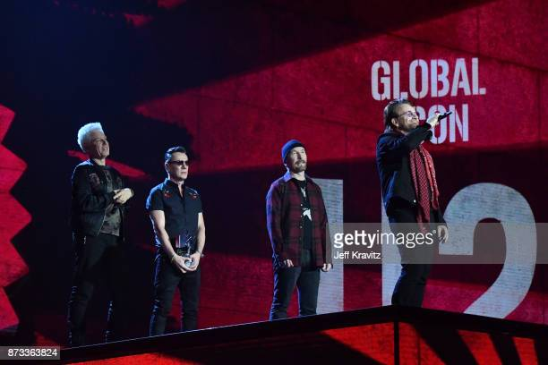 Global Icon award winners Adam Clayton Larry Mullen Jr The Edge and Bono of U2 are seen on stage during the MTV EMAs 2017 held at The SSE Arena...