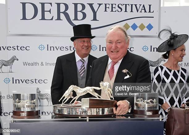 Global Managing Director of Investec Bernard Kantor hands the Investec Derby trophy to Golden Horn owner Anthony Oppenheimer at Derby Day during the...
