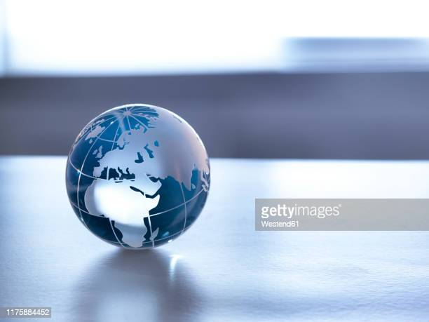 global markets, a glass globe illustrating the world on a desk. - global stock pictures, royalty-free photos & images