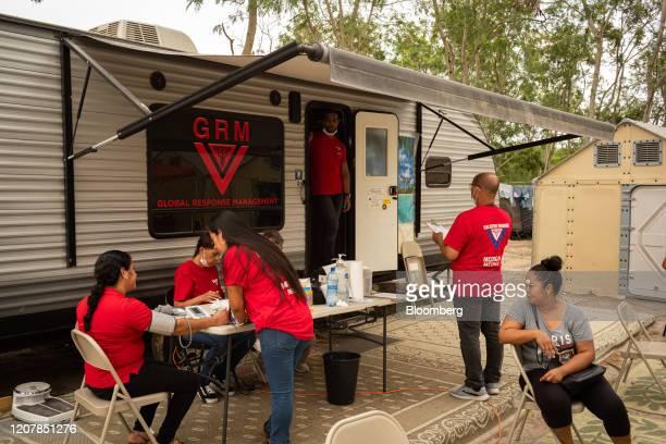 A Global Response Management medical volunteer checks the blood pressure of an asylum seeker at a makeshift migrant camp in Matamoros Tamaulipas...