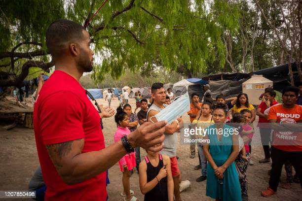A Global Response Management medical volunteer holds a protective mask while teaching asylum seekers about preventative care during the coronavirus...