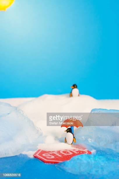 Global warming concept showing penguins on melting ice.