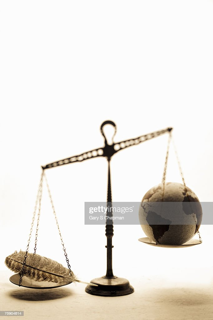 Globe and feather on scales : Stock Photo