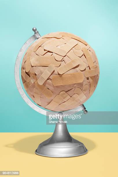 globe covered in bandages - global village stock pictures, royalty-free photos & images