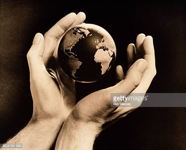 globe floating between pair of man's hands (toned b&w) - world kindness day stock photos and pictures