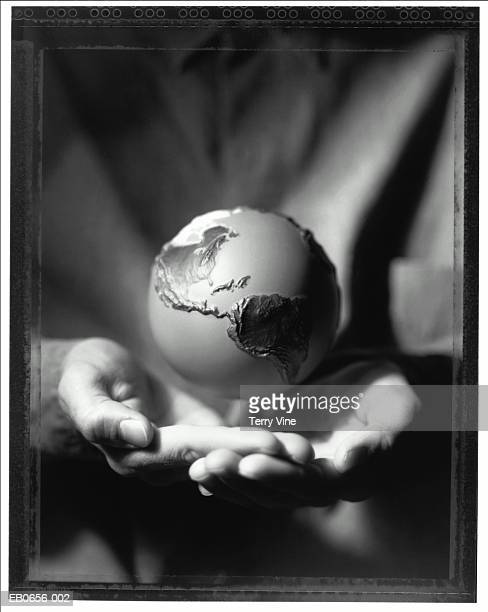 globe hovering above cupped hands, close-up (b&w) - hovering stock pictures, royalty-free photos & images