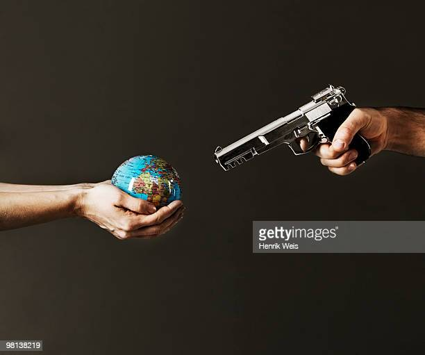 globe in hand with gun aimed at it
