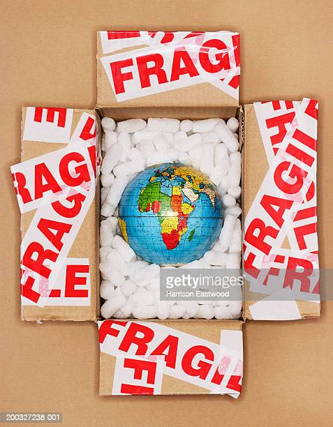 Globe in open packing box covered in tape marked fragile