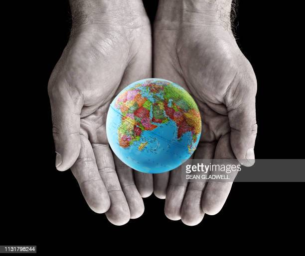 globe in palm of hands - climate stock pictures, royalty-free photos & images