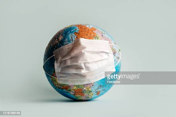 globe made of jigsaw puzzles with a protective medical mask - pandemic illness stock pictures, royalty-free photos & images