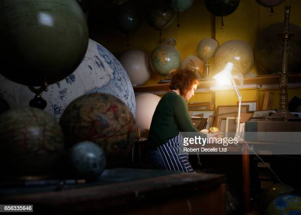 Globe maker examining small globe in workshop
