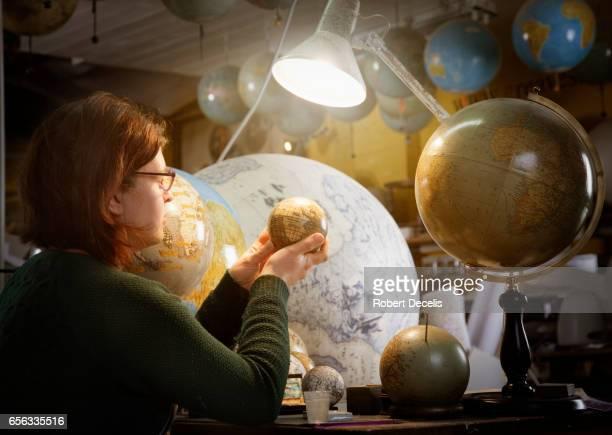 Globe maker examining work in progress