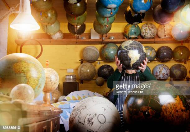 globe maker holding globe in front of face - abundance stock pictures, royalty-free photos & images