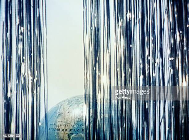 Globe, North America prominent, behind silver curtain (video still)