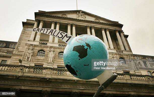 A globe pierced by the scythe of capitalism is held aloft in front of the Bank of England during a protest on October 13 2008 in London The UK...