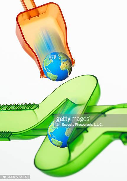 Globe rolling out of orange shovel into green pipe (Digital Composite)