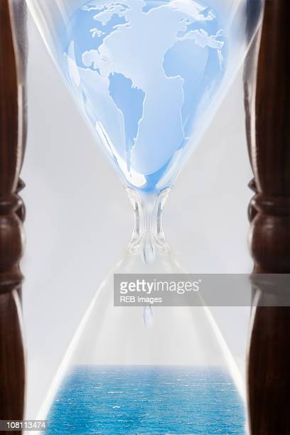 Globe squeezing through hour glass