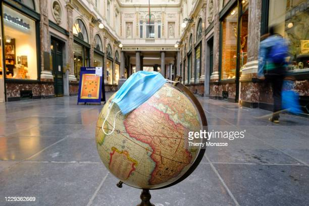 Globe with a surgical mask is seen on the floor of the Galeries Royales Saint-Hubert, on October 28 in Brussels, Belgium. On October 29, the...