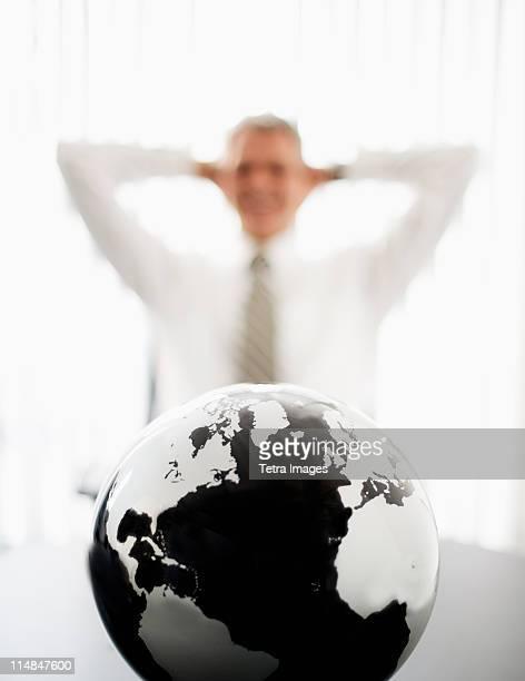 Globe with defocused businessman in background
