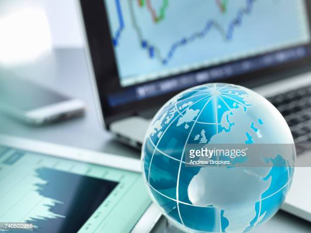 globe with digital tablet, laptop and smartphone showing international business graphs - vintage stock stock pictures, royalty-free photos & images