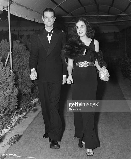 Gloria Baker, social registerite daughter of Mrs. Margaret Emerson, with Howard Hughes, millionaire motion picture producer, pictured leaving The...