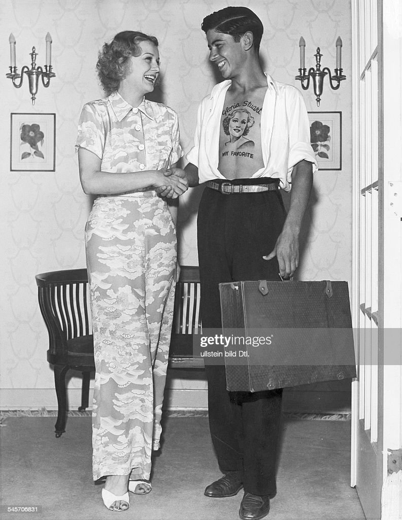 Gloria Frances Stuart, actress. Shaking hands with an admirer, who has painted her name and her portrait on his breast. 1938 : News Photo