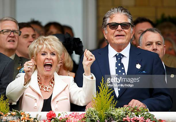 Gloria Hunniford and Stephen Way cheer whilst watching the racing as they attend the Crabbie's Grand National horse racing meet at Aintree Racecourse...