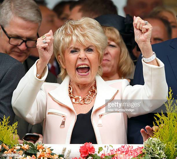 Gloria Hunniford cheers whilst watching the racing as she attends the Crabbie's Grand National horse racing meet at Aintree Racecourse on April 5...