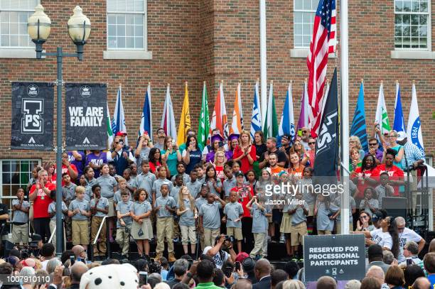 Gloria James mother of LeBron James raises the flag during the opening ceremonies of the I Promise School on July 30 2018 in Akron Ohio The School is...