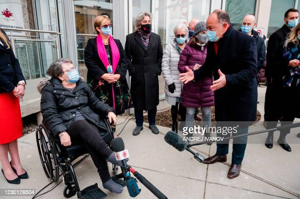 Gloria Lallouz, the first person to be vaccinated at the center, talks to Quebec's Health Minister Christian Dubé during a press conference organized...