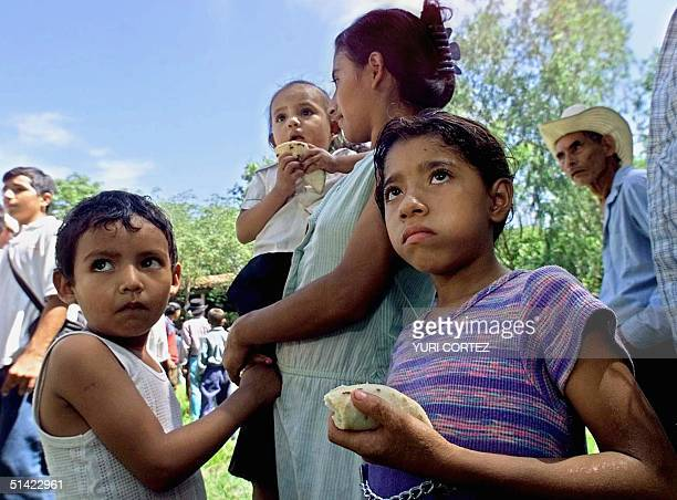 Gloria Orellana with her daughter Brenda three year old son Juan and seven year old daughter Jesica stands in line to receive food rations on August...