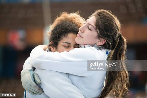 Gloria Perez of Mexico hugs teammate Jocelyn Cruz in celebration of a team victory in the quarterfinals during competition in the Junior Team Women's...