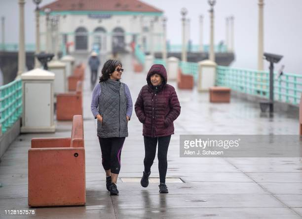 Gloria Puentes left and Margarita Stover both of Hermosa Beach bundle up with rain jackets while walking down the pier amid light rain showers in...