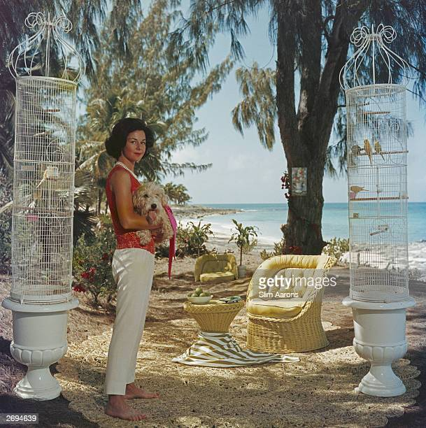 Gloria Schiff the twin sister of Consuelo Crespi with her pet dog and pet birds at Lyford Cay in the Bahamas