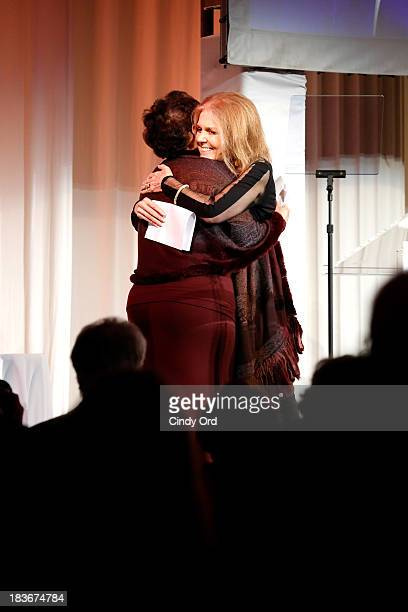 Gloria Steinem and Women's Media Center Visionary Role Model and Corporate Leader Award winner Sheila C Johnson embrace onstage at the 2013 Women's...