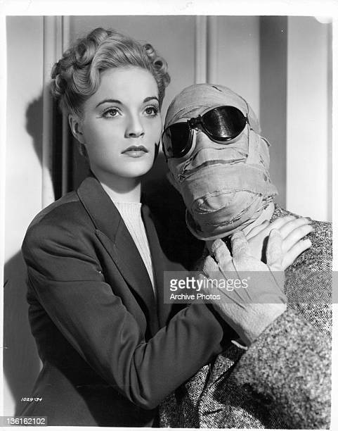 Gloria Stuart has her hand on Claude Rain's chest while he has his head and face completely wrapped in cloth in addition he is wearing sunglasses...
