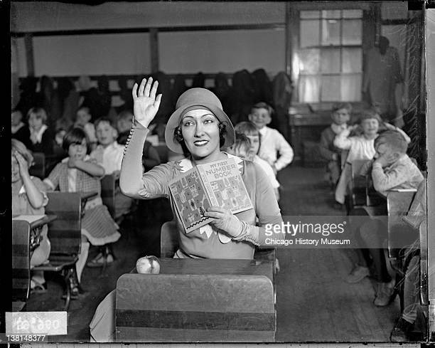Gloria Swanson actress sitting in a desk in a classroom full of children holding up her right hand Chicago Illinois 1929 From the Chicago Daily News...