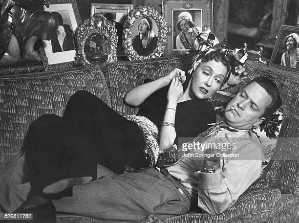 Gloria Swanson as Norma Desmond and William Holden as Joe Gillis recline on a sofa together in the 1950 film Sunset Boulevard
