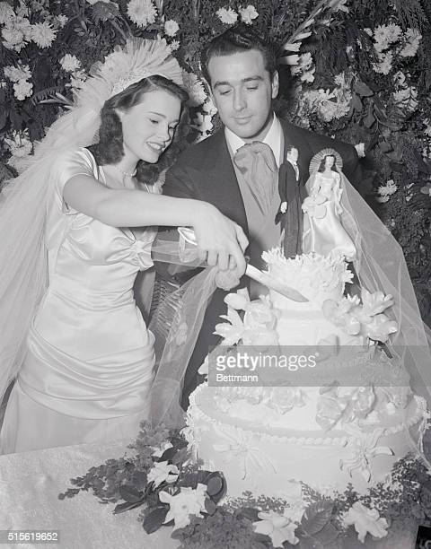 Gloria Vanderbilt DiCicco cuts herself a piece of wedding cake after her marriage to Pasquale Pat DiCicco actor's agent at Santa Barbara