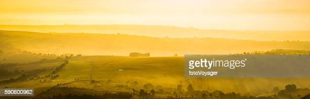 Glorious golden sunrise over idyllic rural hills summer pasture panorama