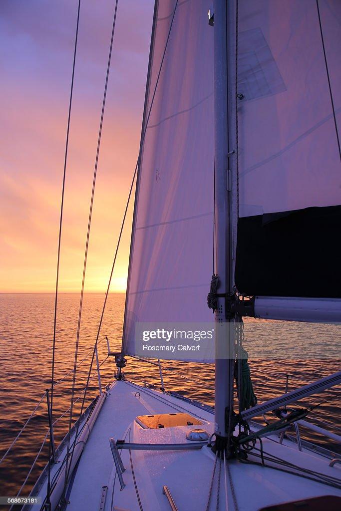 Glorious sunrise and yacht under sail : Stock Photo