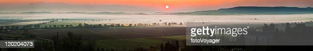 Glorious Tuscan sunrise misty vinyards hilltop palazzo panorama Siena Italy