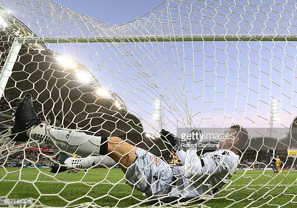 Glory goalkeeper Liam Reddy falls into the back of the net after attempting a save during the round nine ALeague match between Melbourne Victory and...