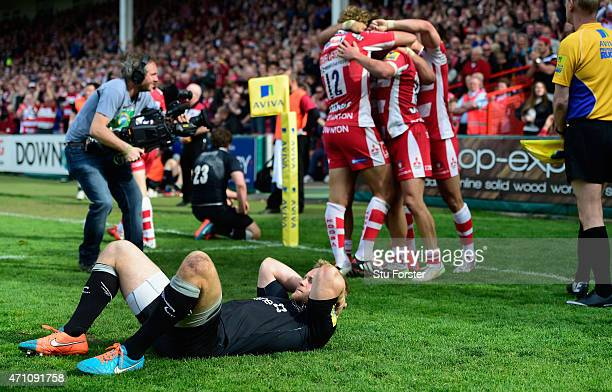 Gloucester players celebrate the winning try scored by Billy Burns as Alex Tait of the Falcons reacts after the Aviva Premiership match between...