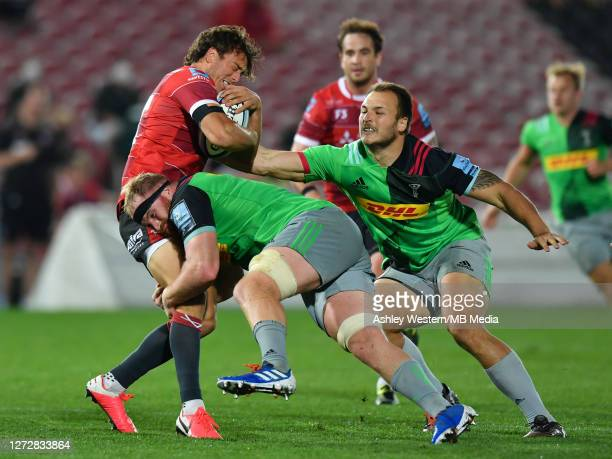 Gloucester Rugby's Lloyd Evans is tackled by Harlequins' James Chisholm and Andre Esterhuizen during the Gallagher Premiership Rugby match between...