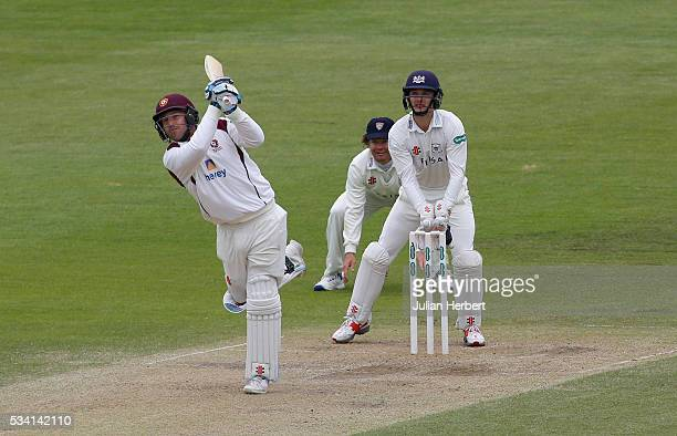 Gloucestershire's Hamish Marshall and wicket keeper Gareth Roderick look on as Northamptonshire's Adam Rossington hits to the boundary during day...