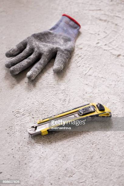 glove and utility knife on the ground - work glove stock photos and pictures